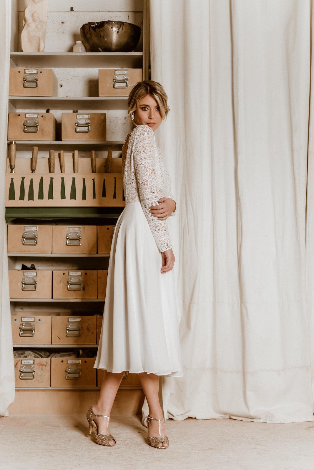noni Jubiläumskollektion | Rückenfreies Midi-Brautkleid aus Boho-Spitze und Crêpe in Ivory, Seitenansicht, Ganzkörperbild (Foto: Le Hai Linh)