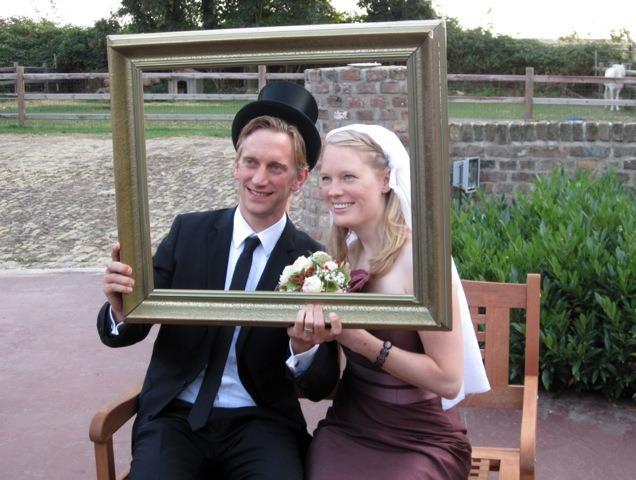 Fotos der Hochzeitsgäste in einem Bilderrahmen mit Schleier und Zylinder