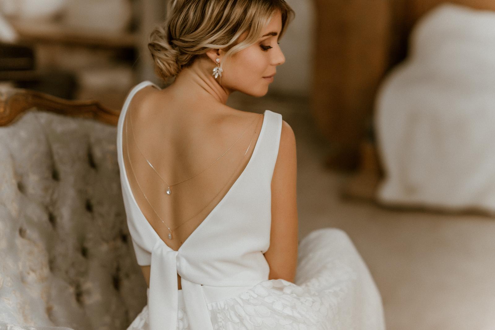 Ärmelloses Brauttop in Ivory mit Rückenausschnitt und Rückenkette, dazu Tüllrock, Rückenansicht
