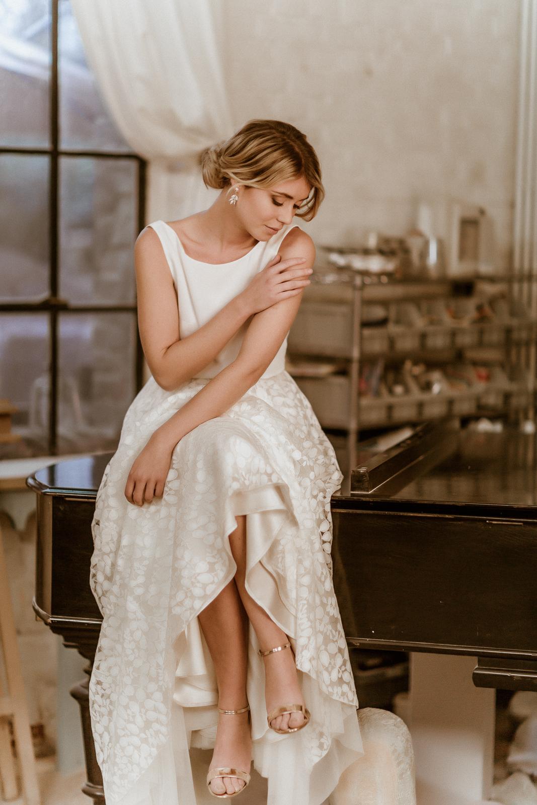 noni Jubiläumskollektion | Ärmelloses Brauttop in Ivory mit Rückenausschnitt und Rückenkette, dazu Tüllrock aus Blätterspitze, Frontalansicht, Modell sitzend (Foto: Le Hai Linh)