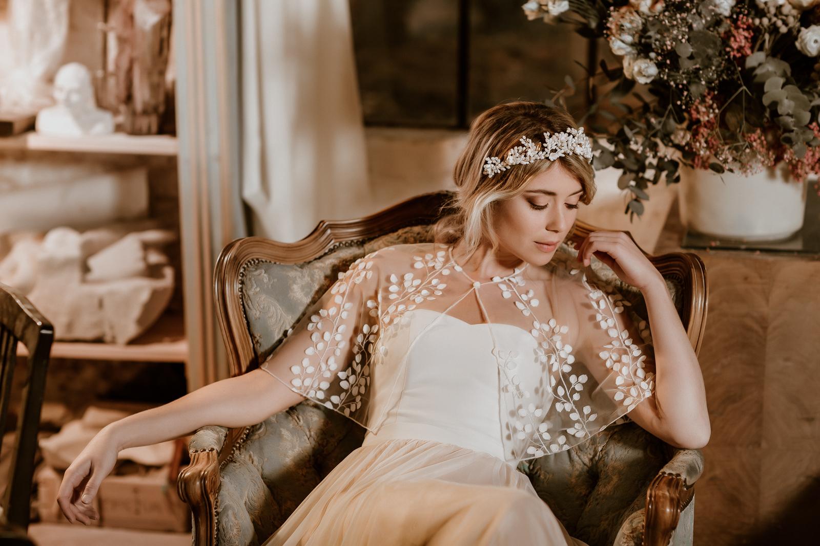 Transparentes Brautcape aus feiner Spitze mit zarten 3D-Blüten, Modell sitzend