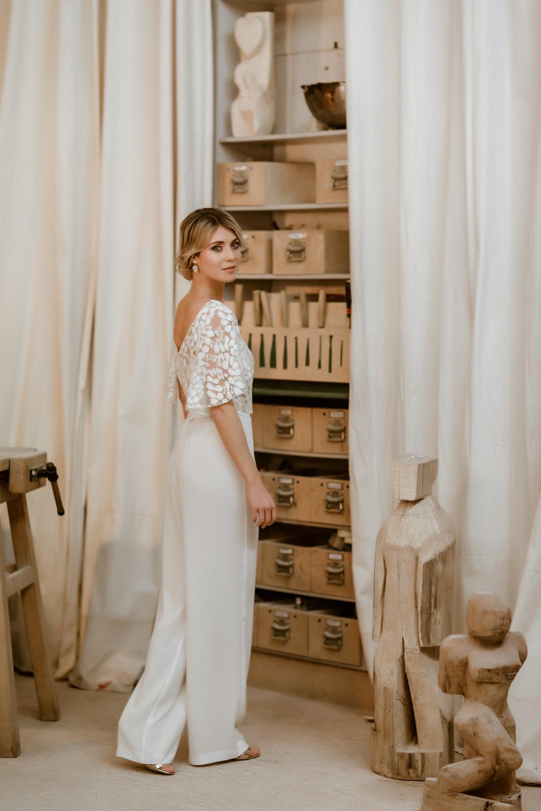 noni Jubiläumskollektion | Spitzentop mit Flügelärmeln und Rückenausschnitt mit langer Brauthose für zweiteiligen Hosenanzug, Ganzkörperbild, Halbprofil (Foto: Le Hai Linh)