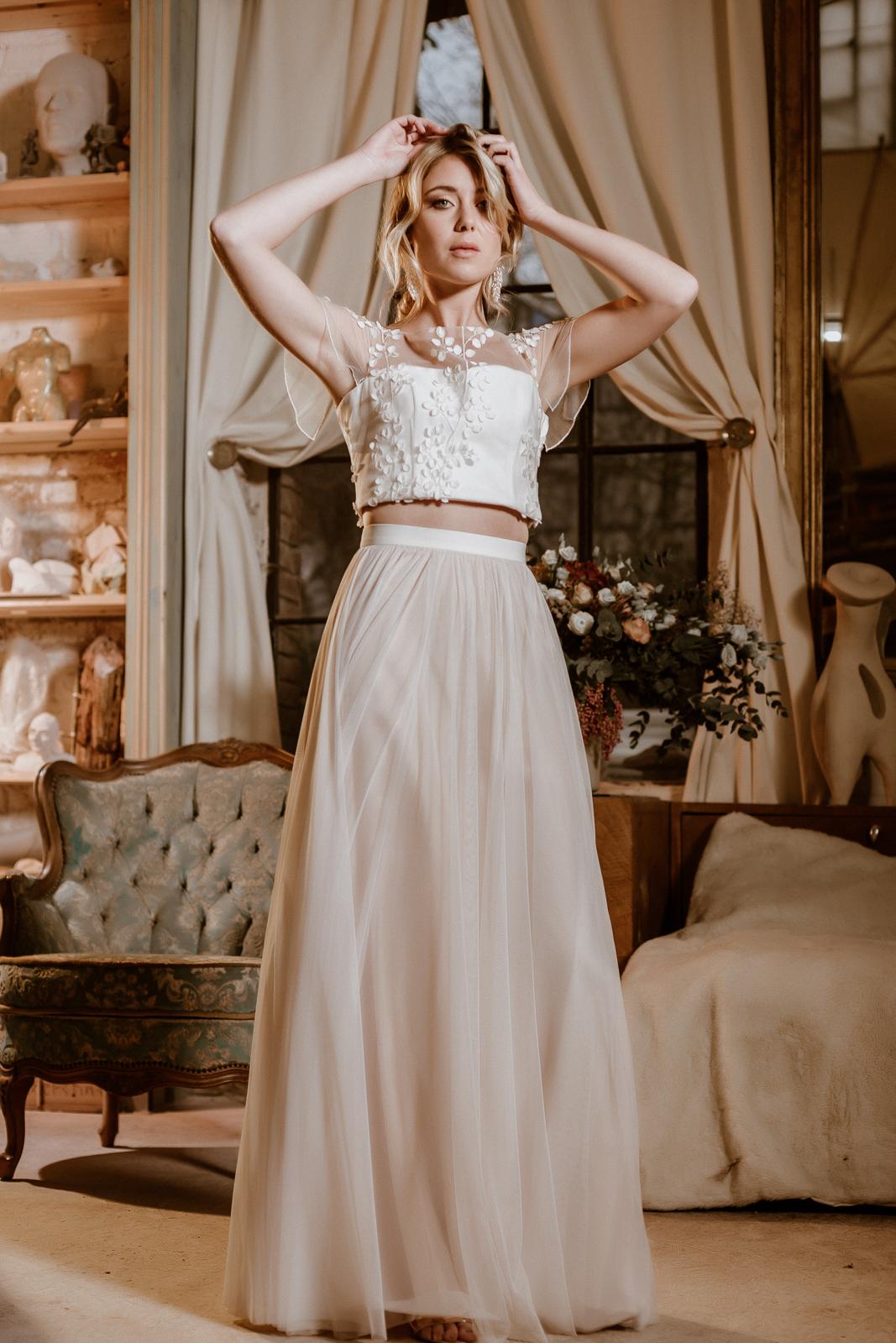 noni Jubiläumskollektion | Brautkleid mit Croptop aus 3D-Spitze und Tüllrock in Ivory-Blush, Frontalansicht, Ganzkörperbild (Foto: Le Hai Linh)