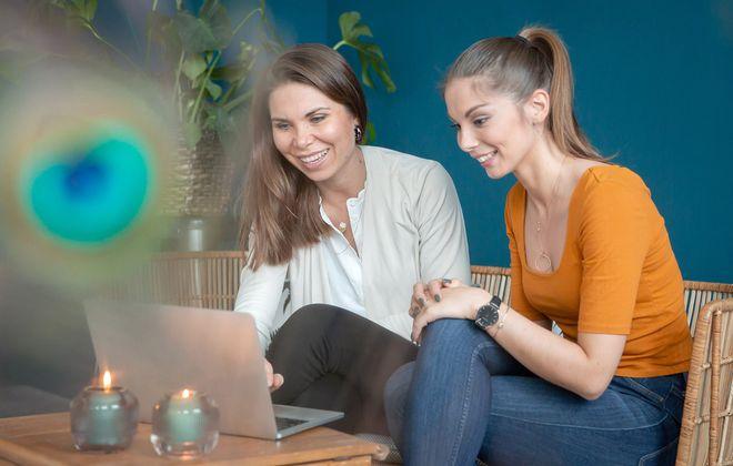 noni Brautkleid kaufen, Moodbild, Freundinnen in Wohnzimmer beim Onlinekauf am Laptop