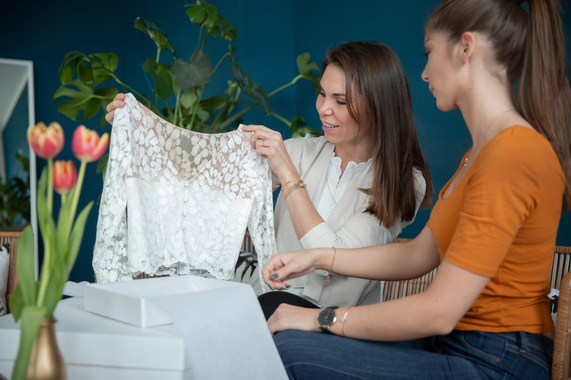 noni Brautkleid kaufen, Moodbild, Freundinnen in Wohnzimmer beim Auspacken von Brautkleid-Sendung