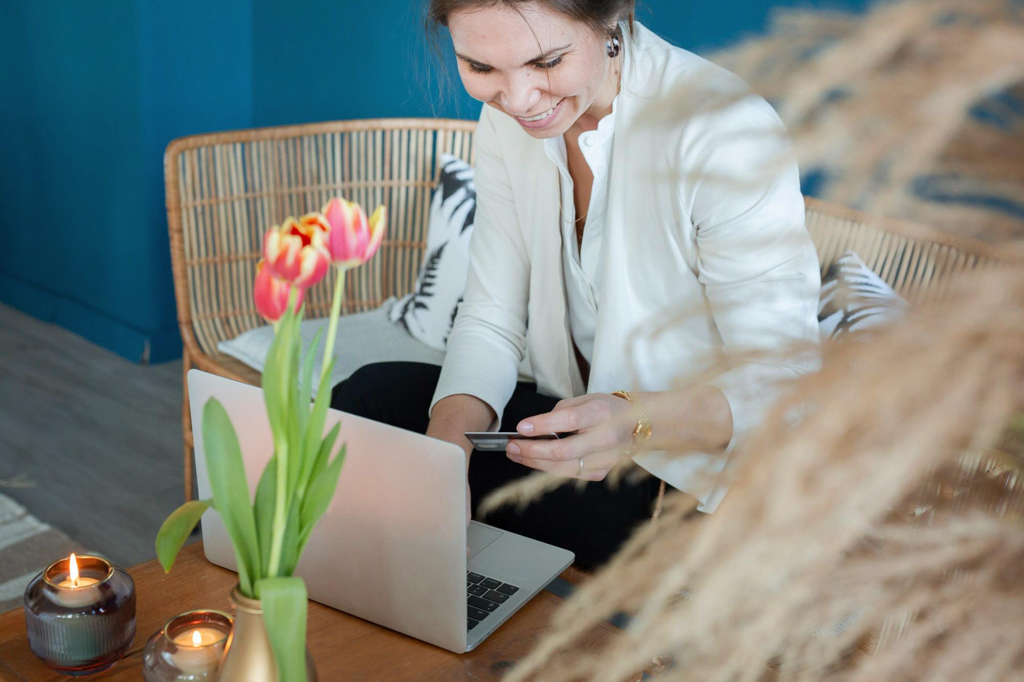 noni Brautkleid kaufen, Moodbild, Frau in Wohnzimmer bei Onlinekauf-Bezahlung mit Laptop