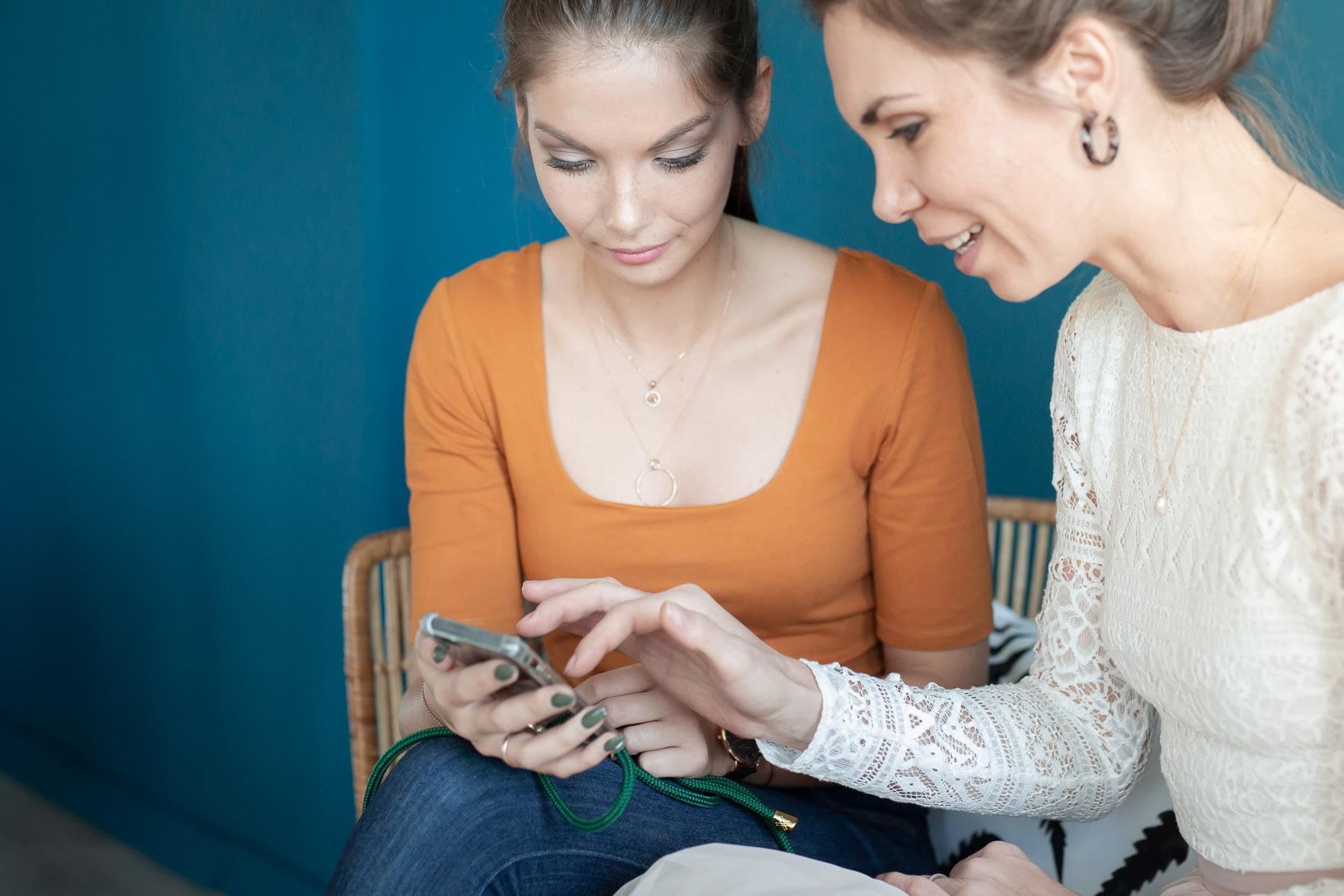 noni Brautkleid kaufen, Moodbild, Freundinnen in Wohnzimmer mit Smartphone