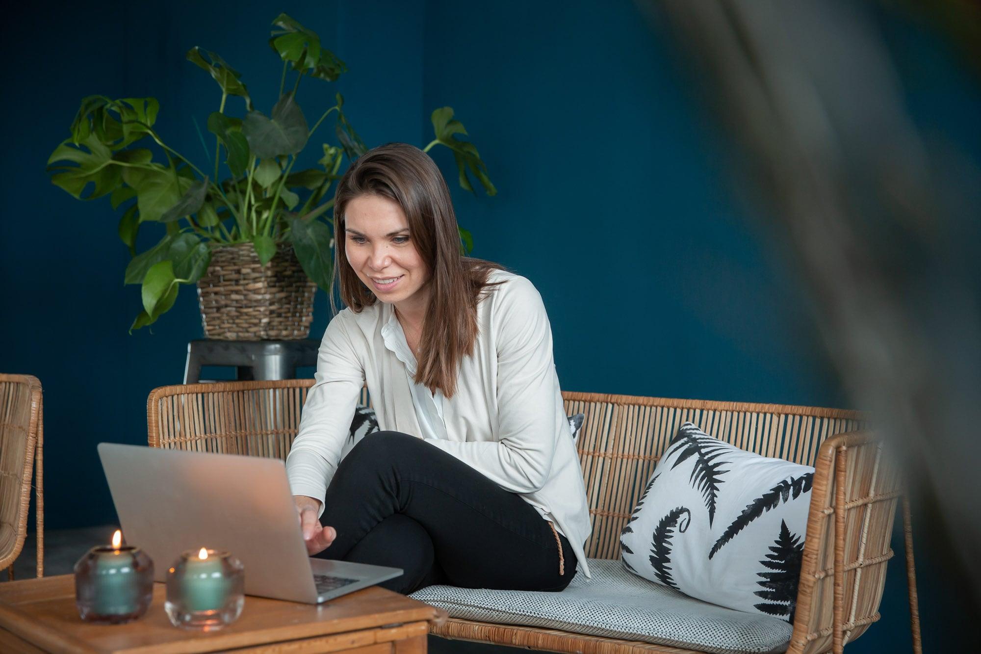 noni Brautkleid kaufen, Moodbild, Frau in Wohnzimmer bei Onlinekauf mit Laptop