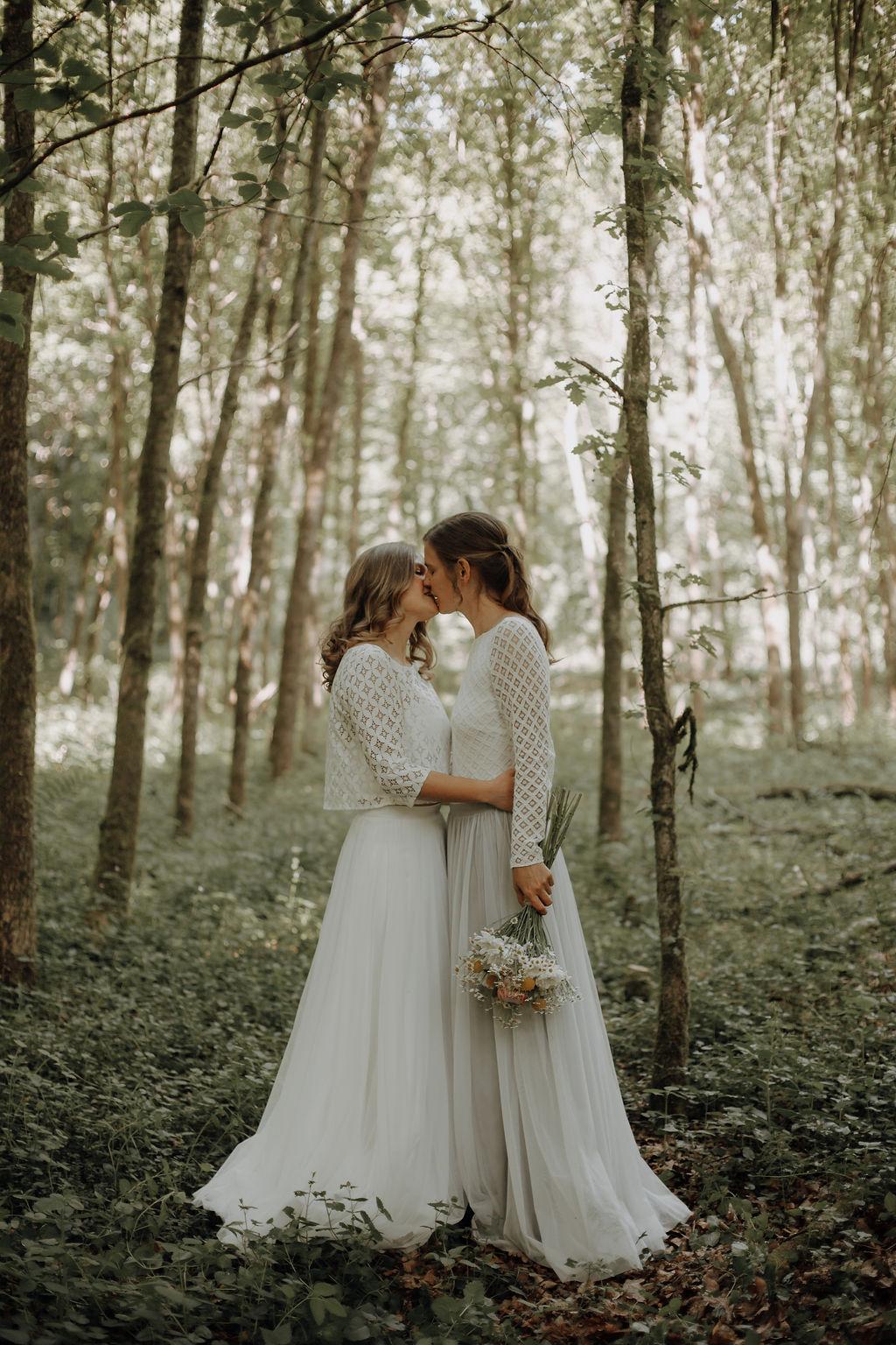 Styled Shoot, lesbisches Brautpaar in zweiteiligen Brautkleidern vor Waldkulisse, küssend