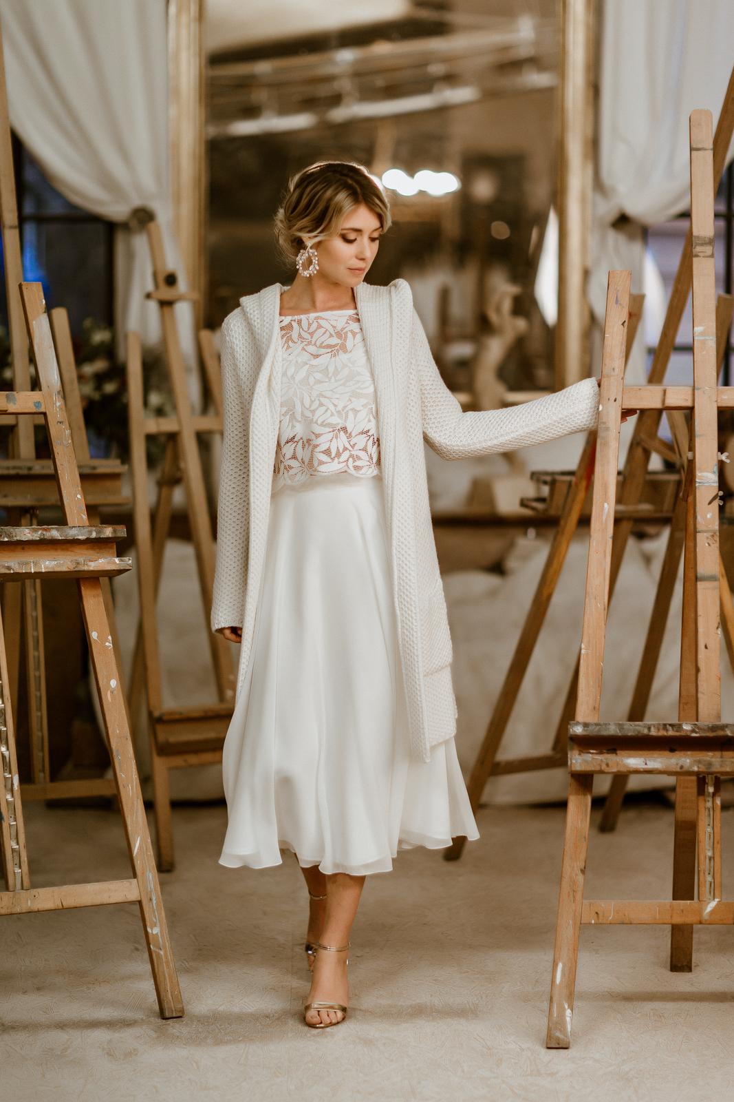 Leichter Brautmantel aus Strick mit Kapuze zum Midi-Brautkleid, frontale Ganzkörperansicht