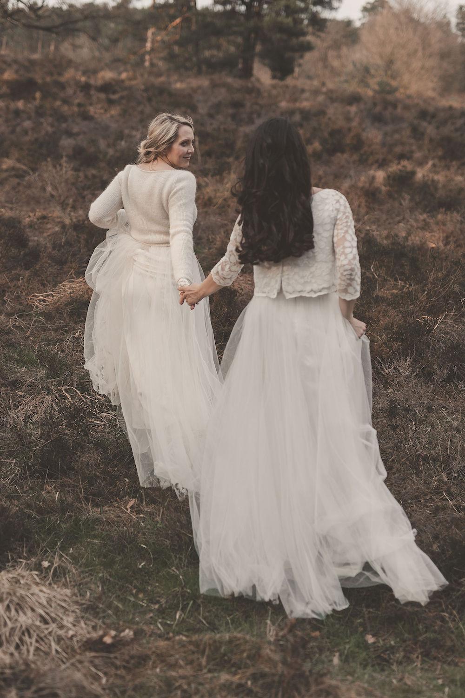 noni Brautmode, Styled Shoot mit lesbischem Brautpaar, Modelpärchen händchenhaltend vor wilder Naturkulisse