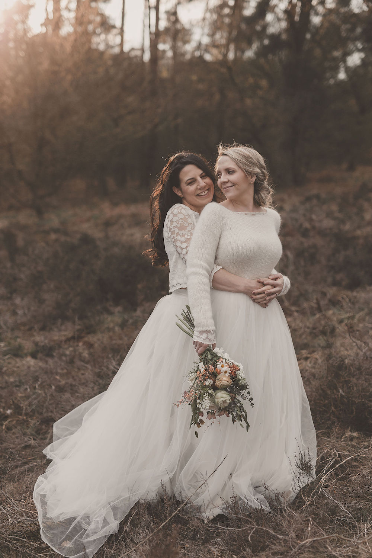 noni Brautmode, Styled Shoot mit lesbischem Brautpaar, brünettes Model mit offenen, langen Haaren und zweiteiligem Brautkleid und blondem Model mit Brautpulli und weißem langem Tüllrock, Brautstrauss haltend
