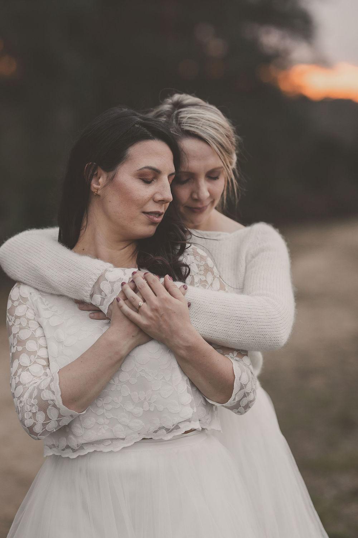 noni Brautmode, Styled Shoot mit lesbischem Brautpaar, sich umarmend. Brünettes Modell mit langen, offenen Haaren und Dreiviertelarm-Top aus weißer Blätterspitze, blondes Model mit Hochsteckfrisur, weißem Strickpulli und herausblitzender Blätterspitze am Ärmel in Weiß