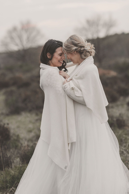 noni Brautmode, Styled Shoot mit lesbischem Brautpaar, Modelpärchen vor wilder Naturkulisse, sich umarmend mit weißer Brautstola umeinander geschlungen