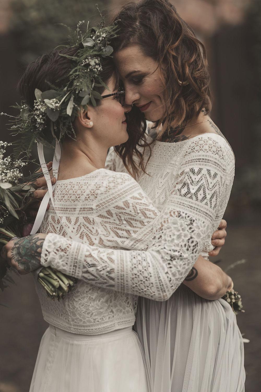 noni Brautmode, Styled Shoot mit lesbischem Brautpaar, sich umarmend. Beide Brautoberteile aus weißer Boho Spitze, Nahaufnahme