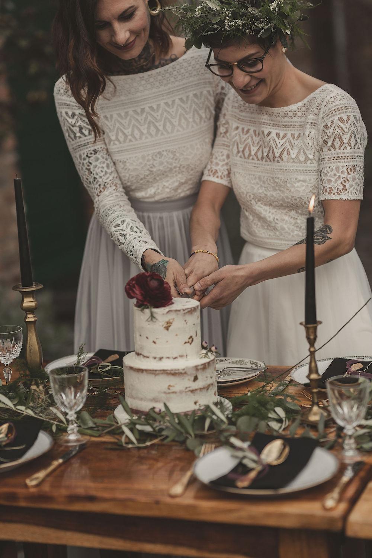 noni Brautmode, Styled Shoot mit lesbischem Brautpaar, sich umarmend. Beide Brautoberteile aus weißer Boho Spitze, Brautröcke aus Tüll in Grau und Weiß, Paar beim Tortenanschnitt