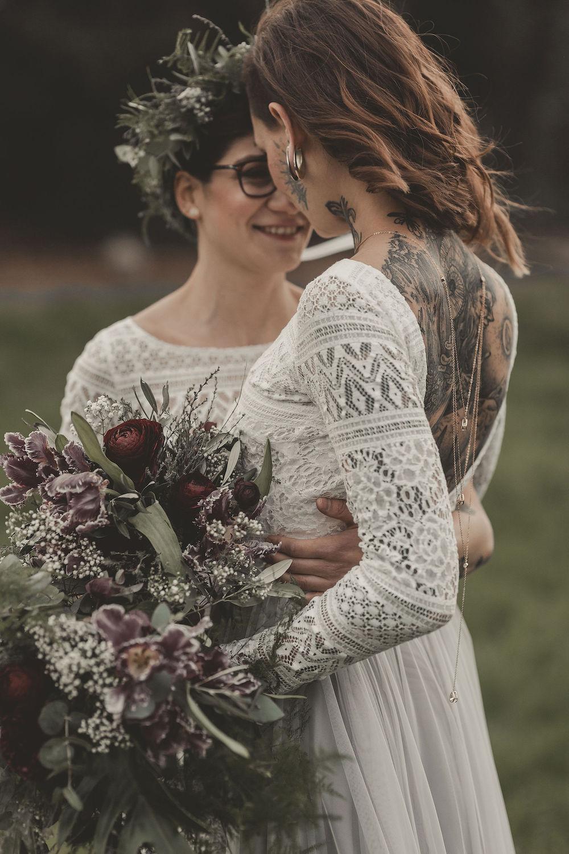 noni Brautmode, Styled Shoot mit lesbischem Brautpaar, sich umarmend. Beide Brautoberteile aus weißer Boho Spitze, Nahaufnahme. Langhaariges Model mit tiefen Rückenausschnitt und tätowiertem Rücken