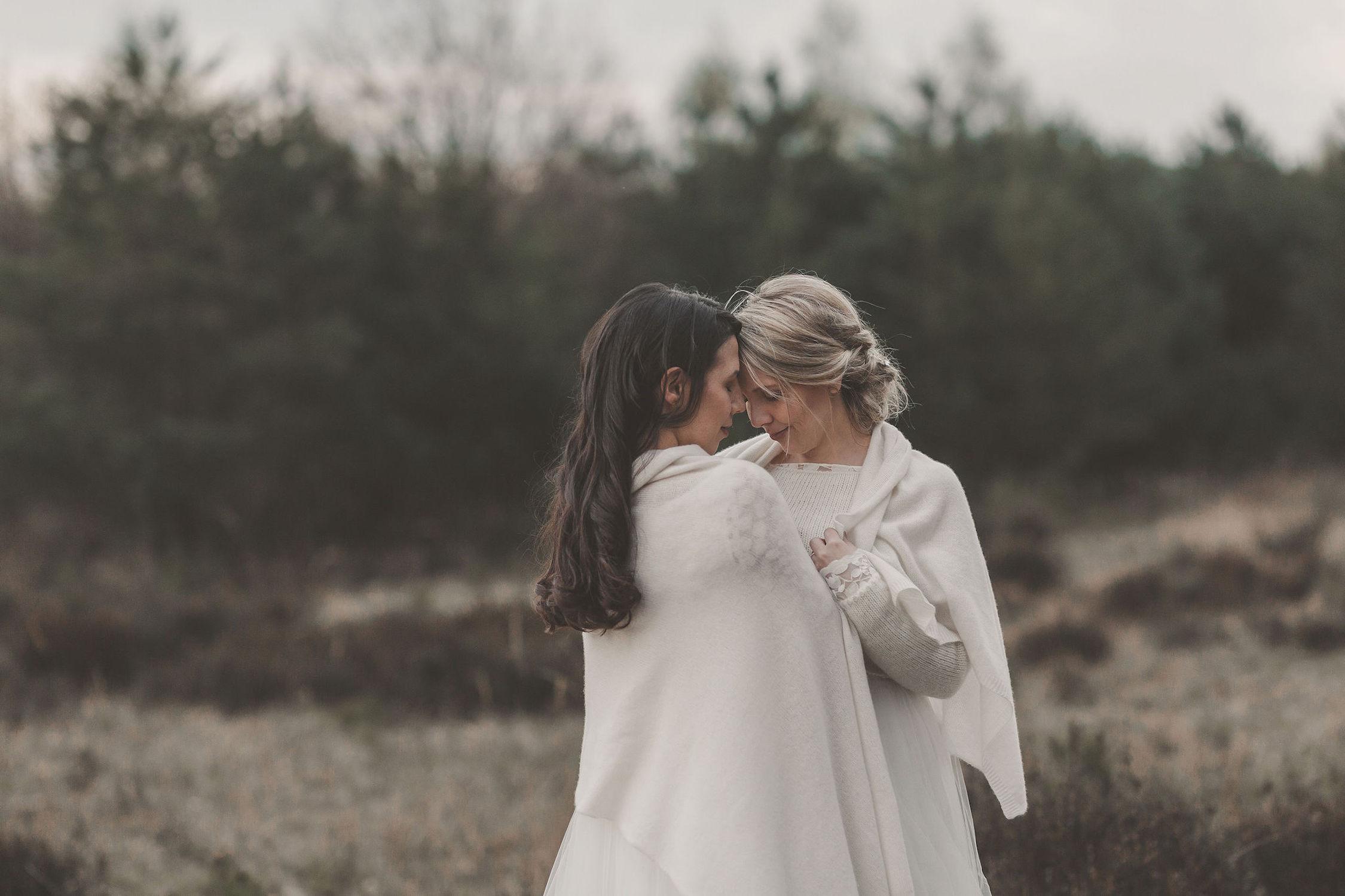noni Brautmode, Styled Shoot mit lesbischem Brautpaar, sich umarmend, mit weißer Brautstola umeinander geschlungen