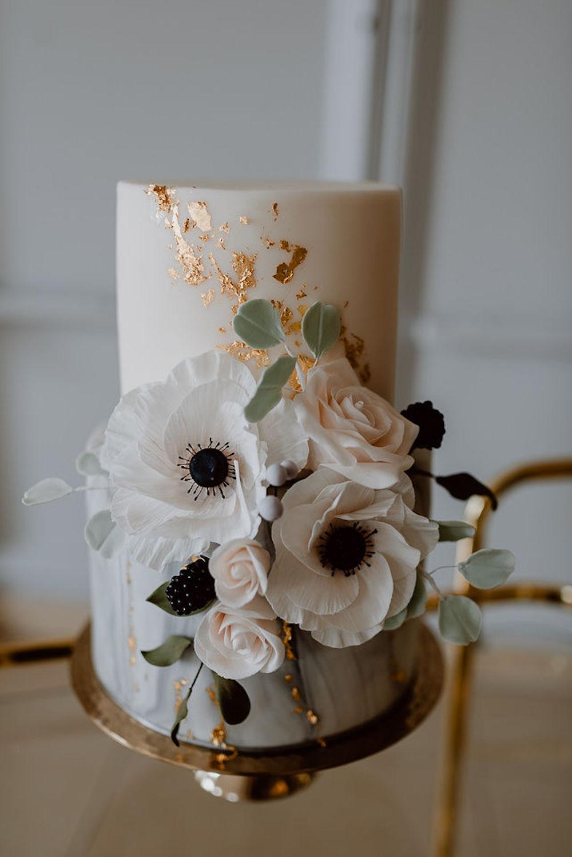 Moderne Hochzeitstorte mit Blütendeko und Blattgold