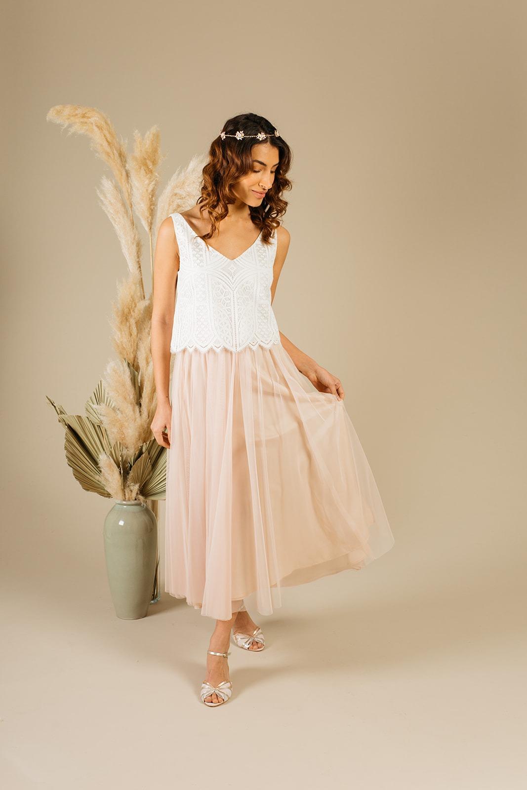 Modell mit zweiteiligem noni-Brautkleid mit rosa Tüfflrock und ärmellosem Boto-Top in Ivory, flache Brautschuhe von Rachel Simspon