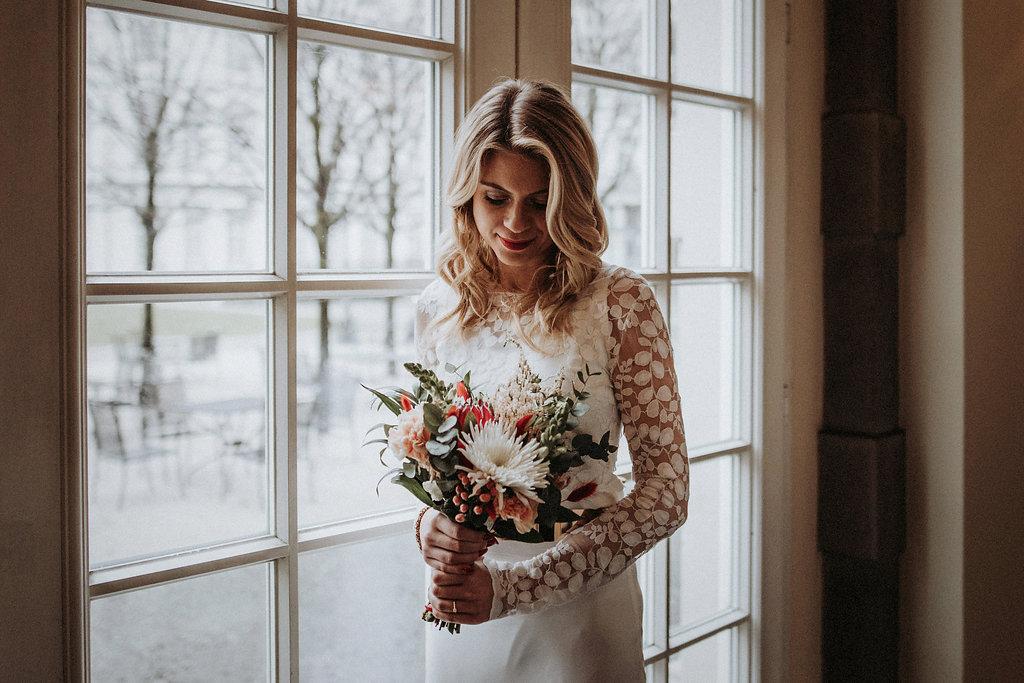 Brautmodel am Fenster mit Blumenstrauß