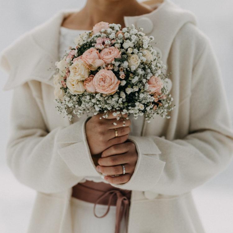 Winterhochzeit im Schnee mit Brautmantel und zweiteiligem Brautkleid