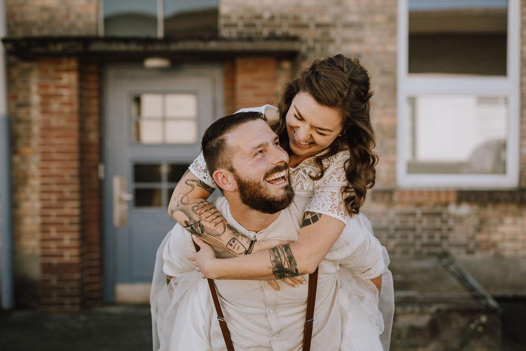 Styled Shoot Brautmode, Bräutigam Braut auf dem Rücken tragend, lachend