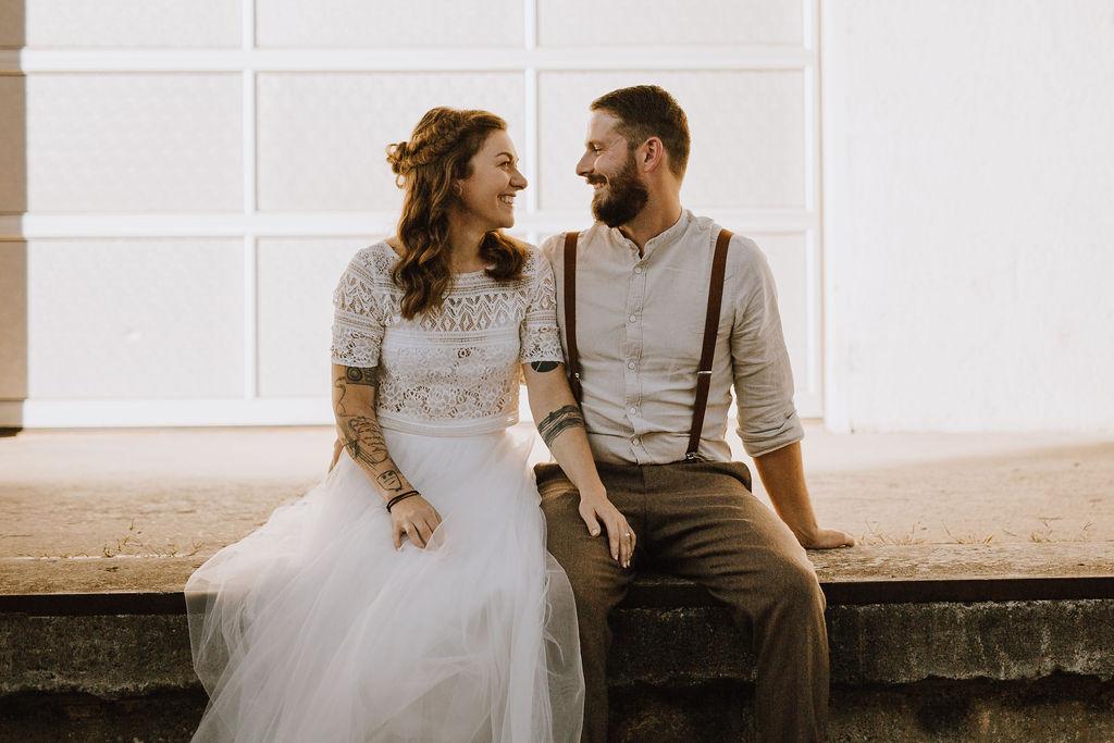 Styled Shoot, Brautpaar mit Boho Brautkleid zweiteilig, nebeneinander auf Mauer sitzend
