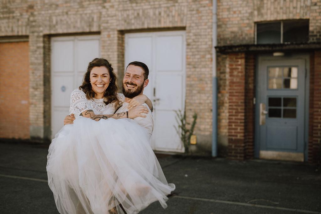 Styled Shoot, Boho-Brautpaar, Bräutigam Braut tragend, lachend