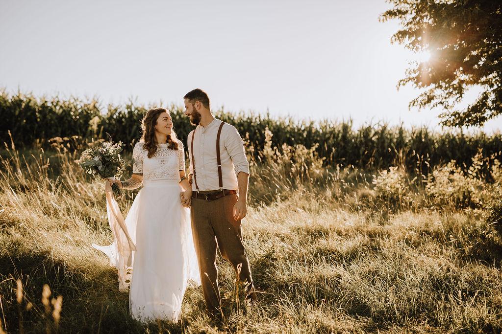 Styled Shoot Boho Hochzeit, Brautpaar nebeneinander auf wilder Wiese
