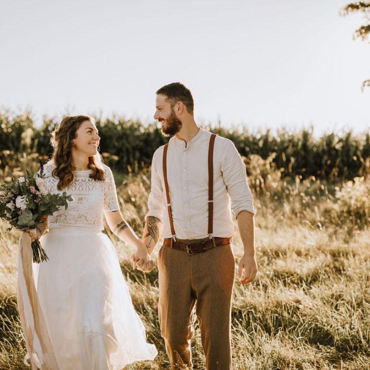 Styled Shoot Boho Hochzeit, Brautpaar nebeneinander auf wilder Wiese, händchenhaltend