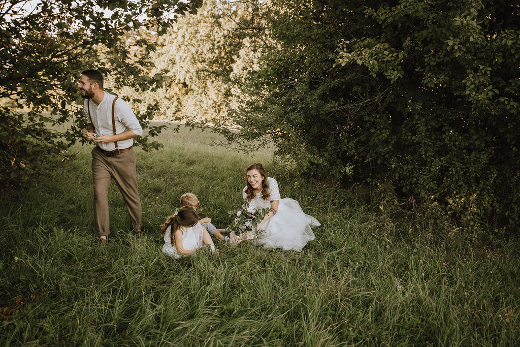 Styled Shoot Boho Hochzeit, Moodbild, Braut mit Kind auf Wiese sitzend