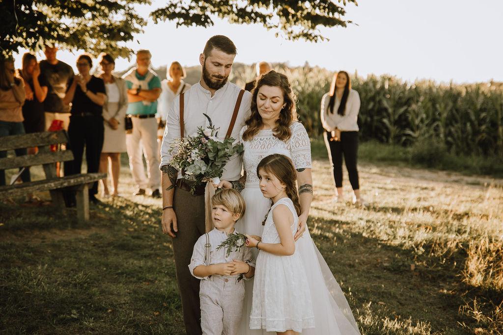 Styled Shoot Boho Hochzeit, freie Trauung auf Wiese, Hochzeitsgäste, Brautpaar und Kinder