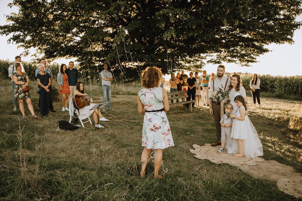 Styled Shoot Boho Hochzeit, freie Trauung auf Wiese, Hochzeitsgäste, Hochzeitsrednerin, Brautpaar und Kinder