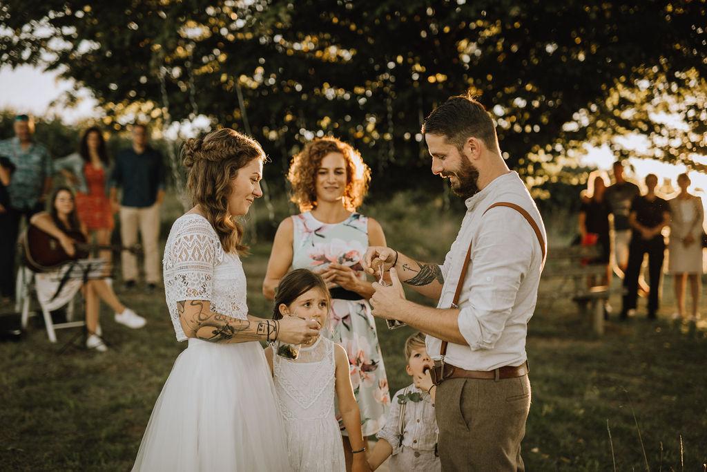 Styled Shoot Boho Hochzeit, freie Trauung auf Wiese, Hochzeitsgäste, Hochzeitsrednerin, Brautpaar und Kinder, Ringtausch