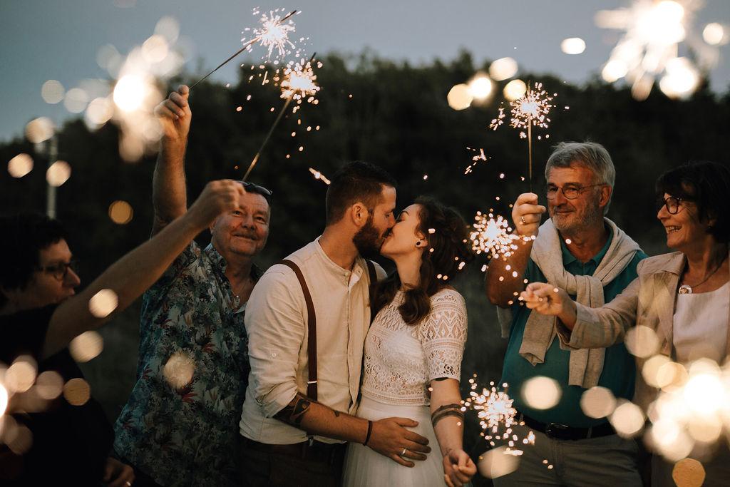 Styled Shoot Boho Hochzeit, Outdoor Hochzeit, Hochzeitsgäste mit Wunderkerzen und Brautpaar