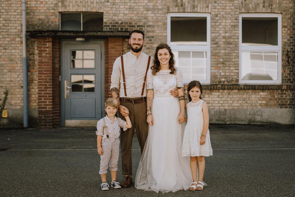 Styled Shoot Brautmode, Brautpaar mit zweiteiligem Boho Brautkleid, brauner Anzugshose, Hemd und Boho-Hosenträgern, Gruppenbild mit zwei Kindern