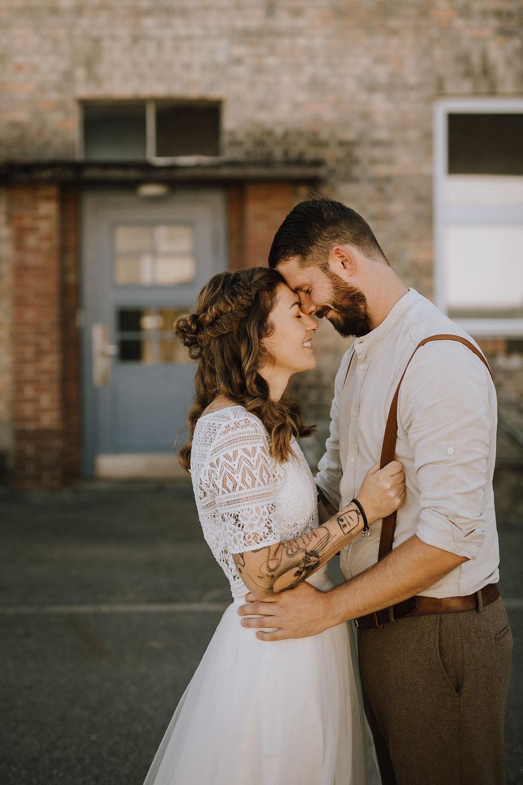 Styled Shoot Brautmode, Brautpaar mit zweiteiligem Boho Brautkleid, brauner Anzugshose, Hemd und Boho-Hosenträgern, umarmend