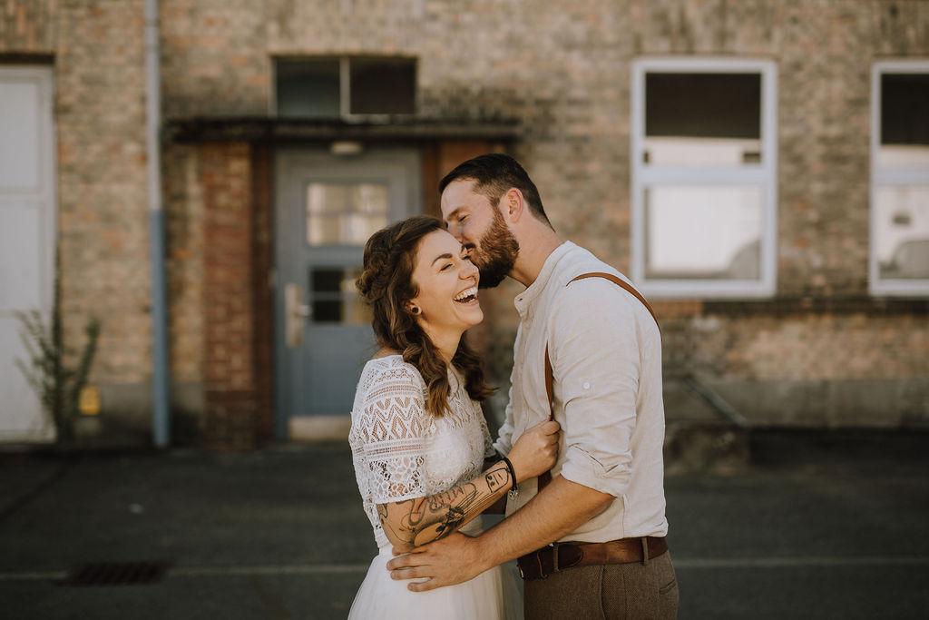 Styled Shoot Brautmode, Brautpaar mit zweiteiligem Boho Brautkleid, brauner Anzugshose, Hemd und Boho-Hosenträgern