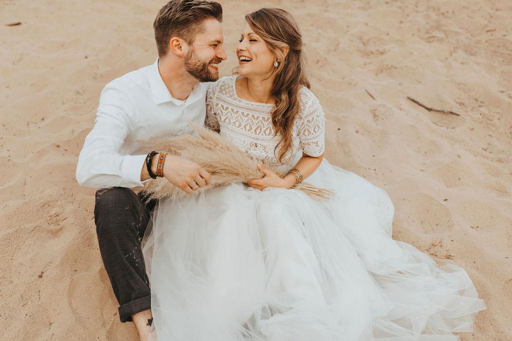 Styled Shoot Brautmode am Strand, Model-Brautpaar, sitzend. Braut mit Kurzarm-Top aus Boho-Spitze und langem Tüllrock in Ivory, lachend
