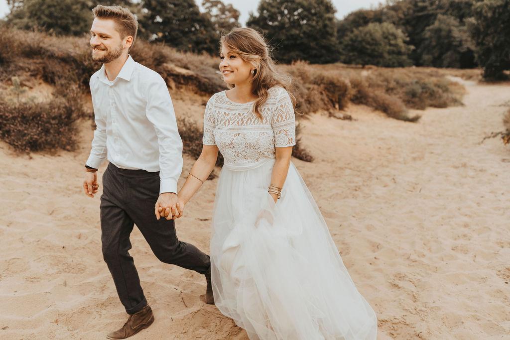 Styled Shoot Brautmode am Strand, Model-Brautpaar, sitzend. Braut mit Kurzarm-Top aus Boho-Spitze und langem Tüllrock in Ivory, spazierend am Strand