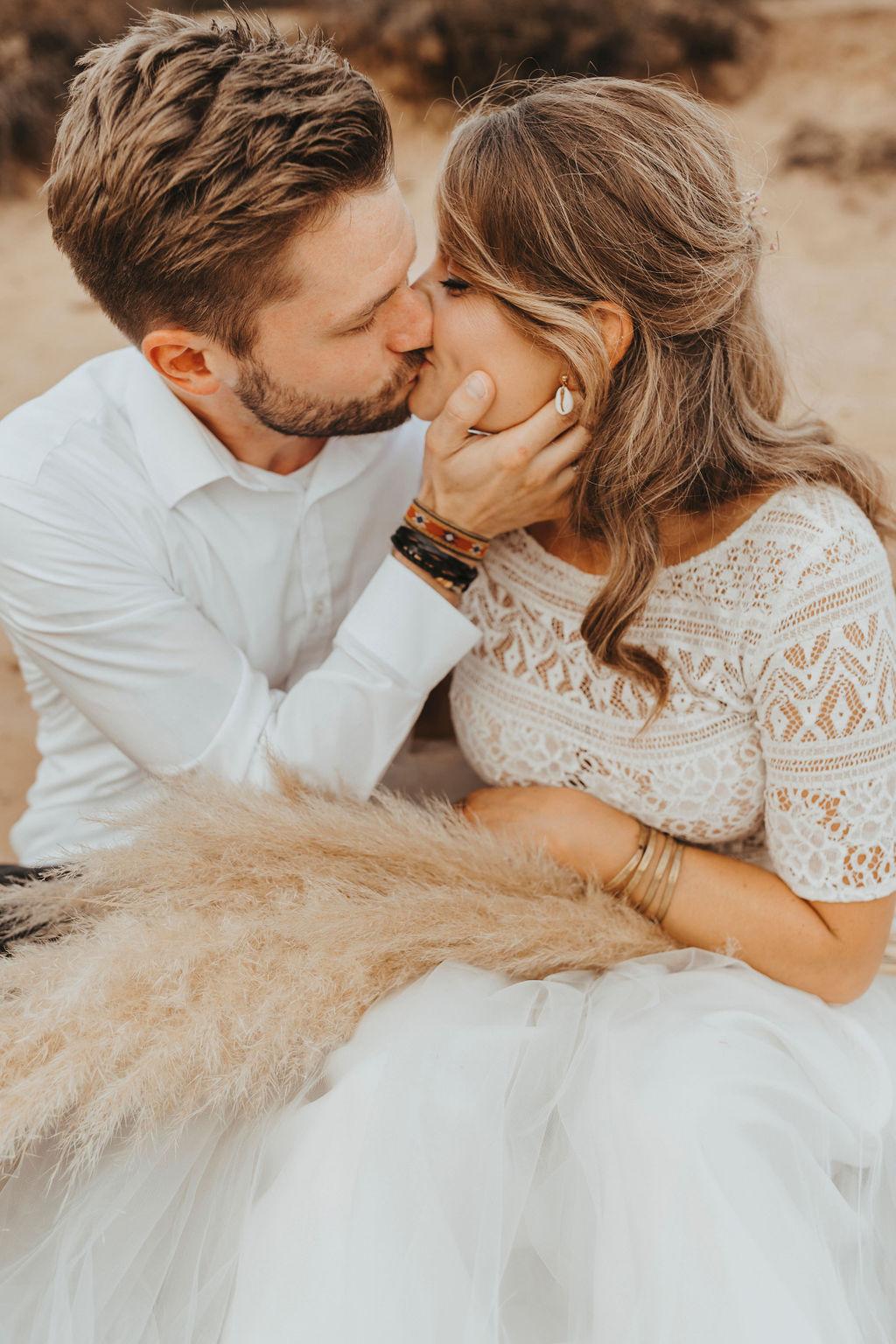 Styled Shoot Brautmode am Strand, Model-Brautpaar, sitzend. Braut mit Kurzarm-Top aus Boho-Spitze und langem Tüllrock in Ivory, küssend