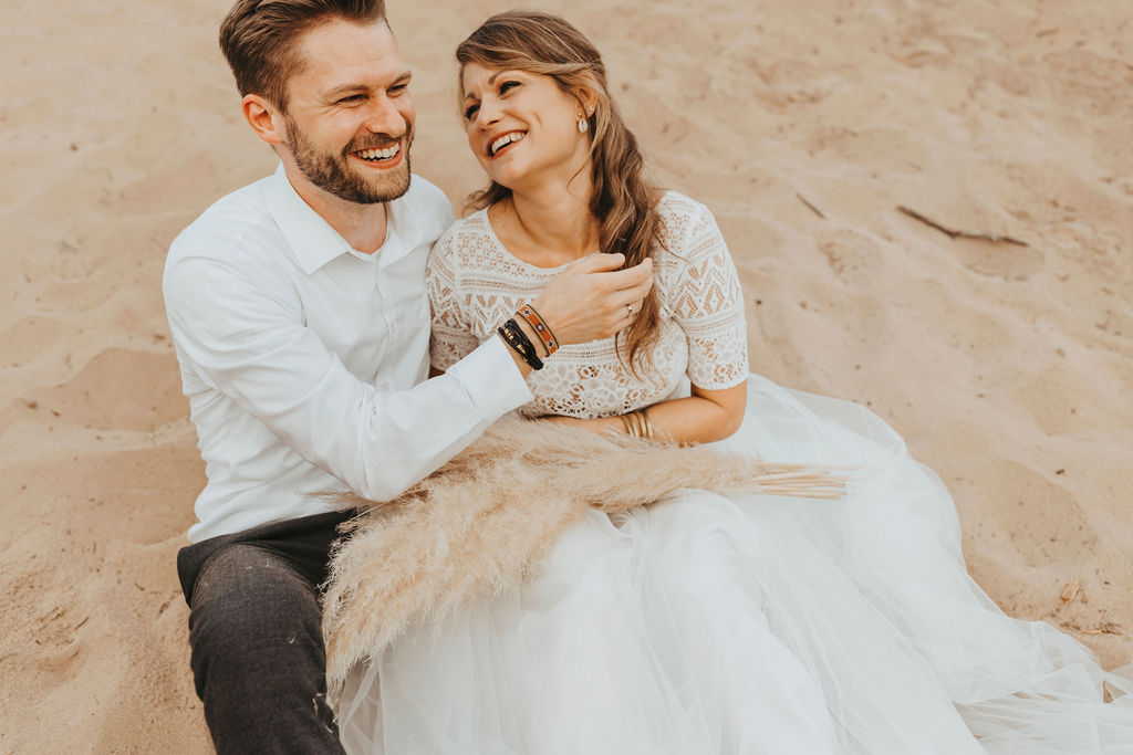 Styled Shoot Brautmode am Strand, Model-Brautpaar, sitzend. Braut mit Kurzarm-Top aus Boho-Spitze und langem Tüllrock in Ivory