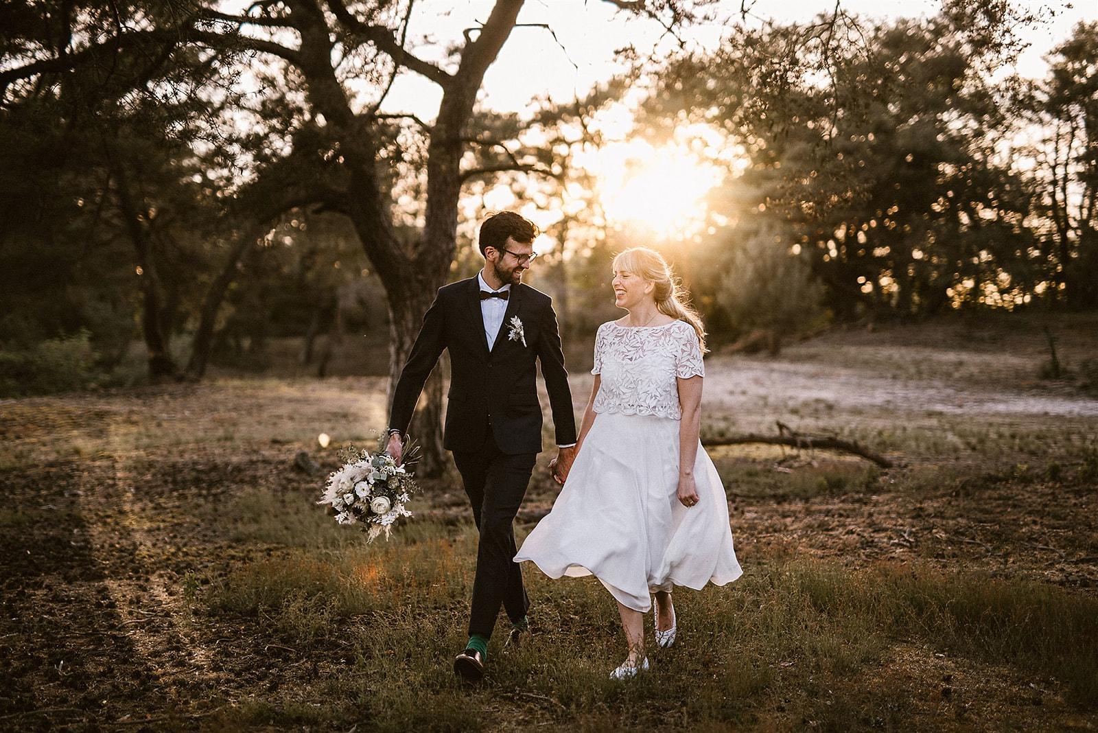 Brautpaar händchenhaltend, schwungvoll spazierend auf Wiese