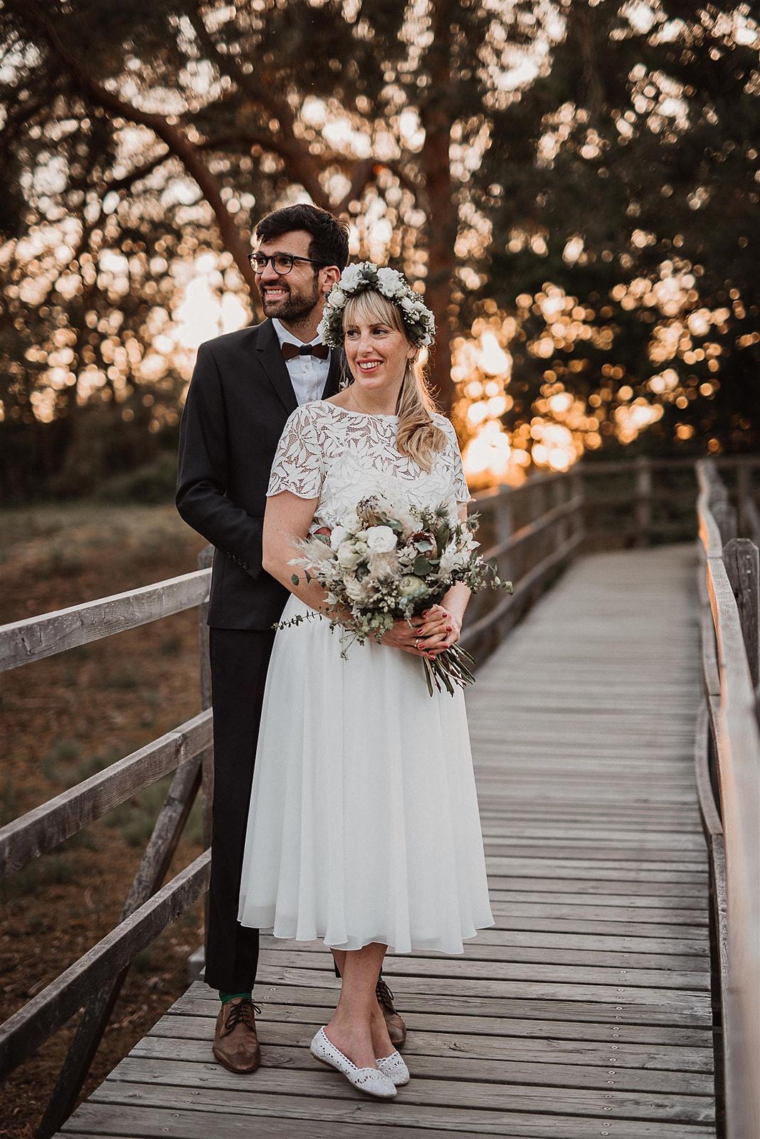 Brautpaar auf Brücke im Sonnenuntergang stehend, Braut mit wadenlangem Chiffonrock und Kurzarmtop aus Blätterspitze, Brautstrauss haltend, Blumenkranz im Haar, passend zum Strauss. Bräutigam mit dunklem Anzug