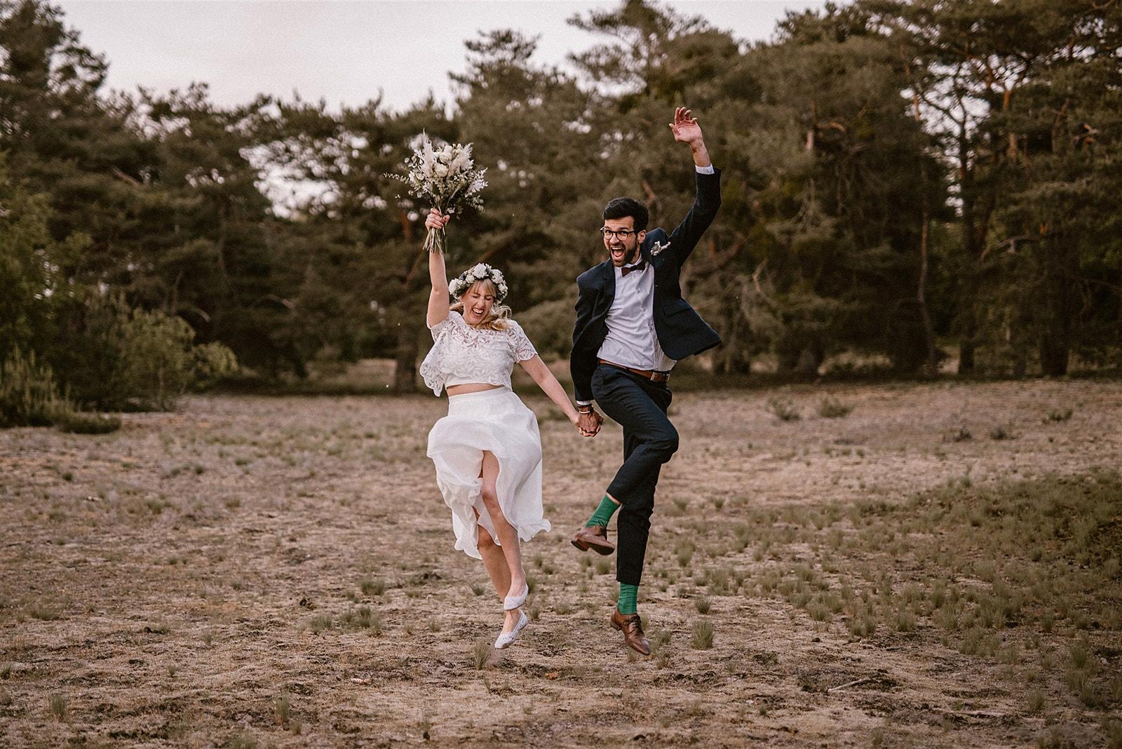 Brautpaar händchenhaltend, Hände in die Luft werfend und springend auf Feld