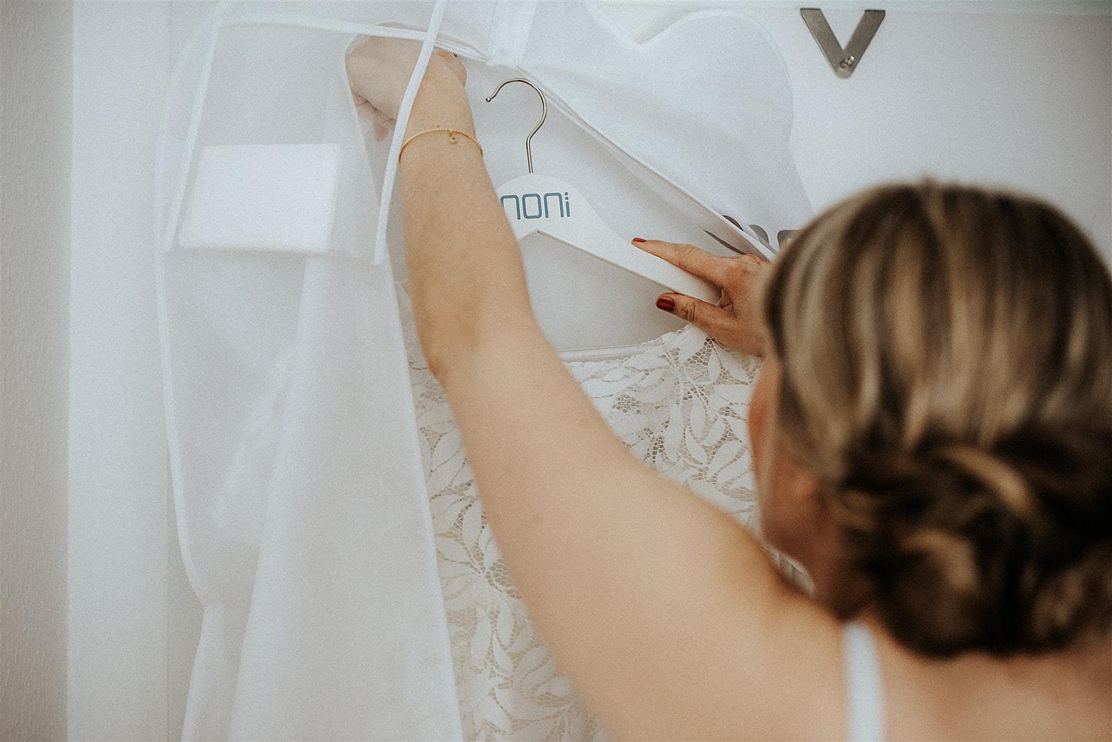noni Brautmode, Braut nimmt Brautkleid aus Kleidersack während Getting Ready Shooting