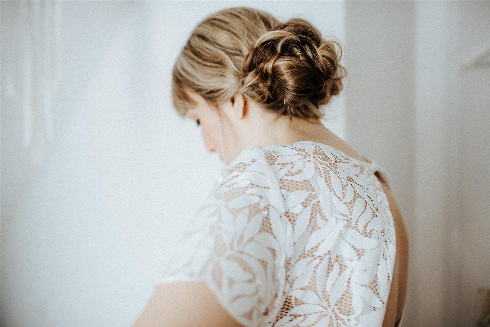 noni Brautmode, Getting Ready Shoot, blonde Braut mit Hochsteckfrisur und Kurzarmtop aus halb-transparenter Blätterspitze, Rückenansicht