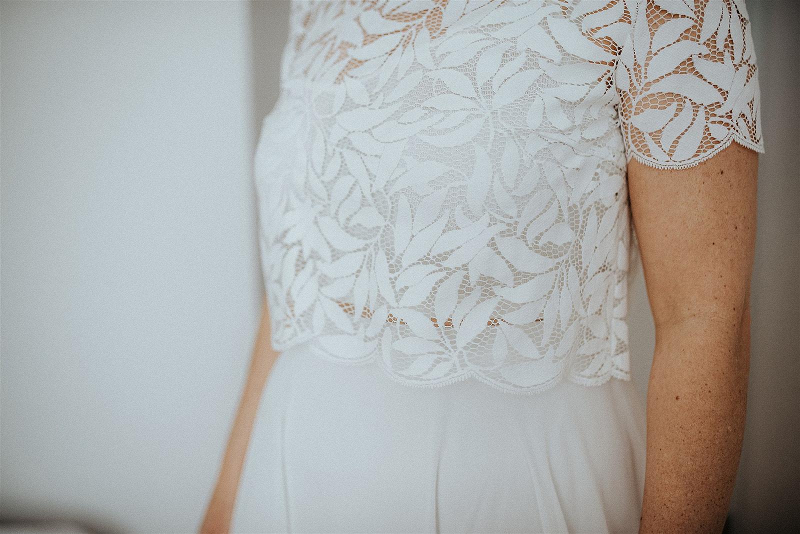noni Brautmode, Getting Ready Shoot, kurzärmeliges Brauttop aus Spitze mit Blättermuster und Bogensaum, halb-transparent, Nahaufnahme