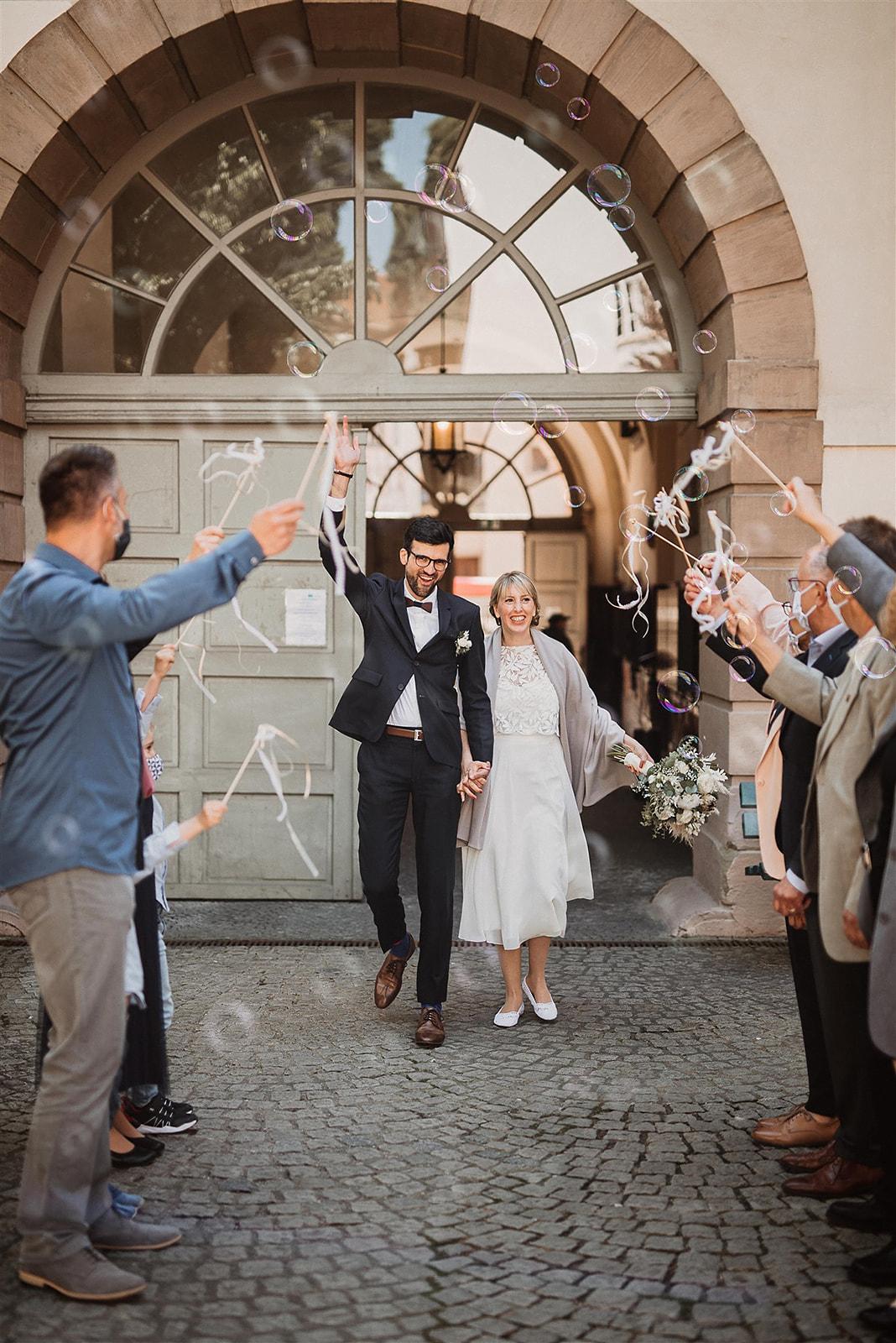 noni Brautmode, Brautpaar händchenhaltend tritt aus Standesamt in Freie, Gäste schmeissen Luftschlangen und lassen Seifenblasen fliegen. Bräutigam in dunklem Anzug, Braut mit midi-langem Zweiteiler mit wadenlangem Rock und Top aus Botanikspitze